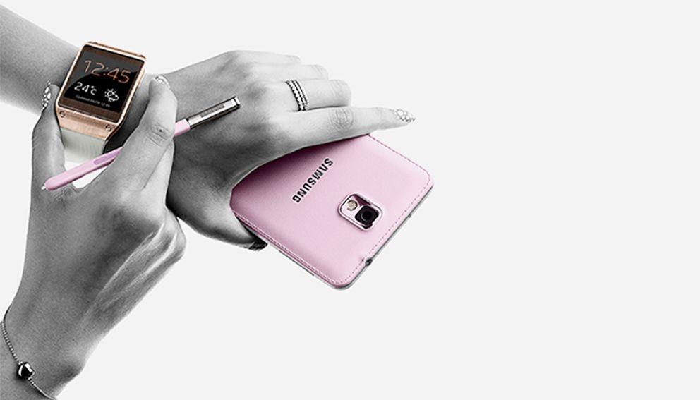 Mains de femme tenant un téléphone Samsung rose et regardant l'heure sur sa montre connectée