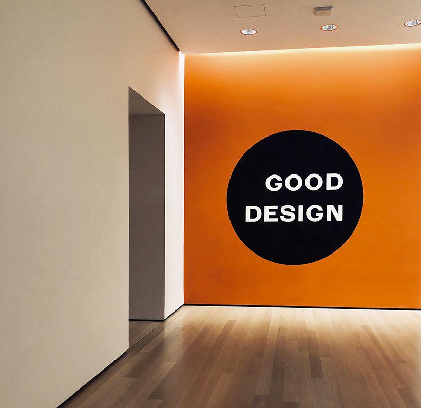 Mur orange avec inscription Good design sur rond noir