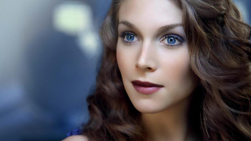 Gros plan visage de femme brune avec yeux très bleus utilisant produit gouttes bleues