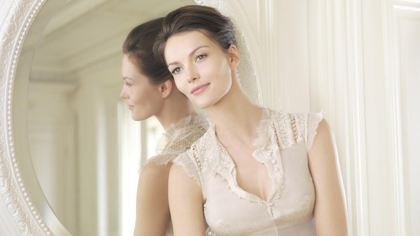 Femme souriante dans appartement haussmannien adossée à un miroir